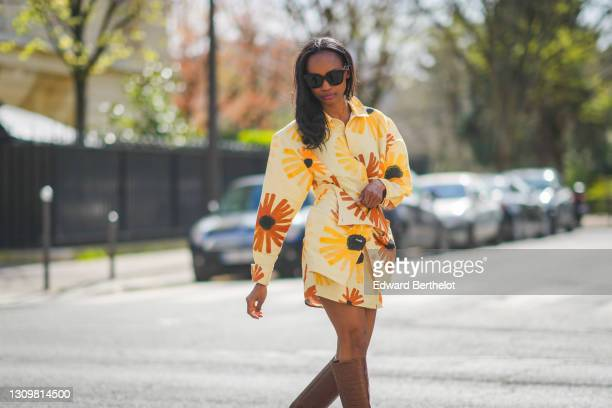 Emilie Joseph @in_fashionwetrust wears a yellow and orange floral print Jacquemus Murano dress with flap pockets and buttoned waist, on March 28,...