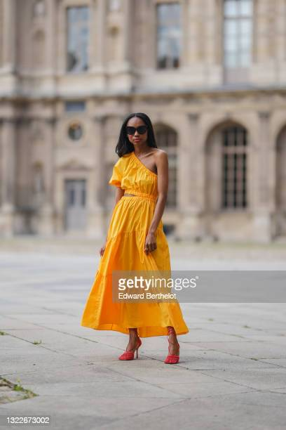 Emilie Joseph @in_fashionwetrust wears a yellow asymmetric cut-out midi dress from Mango, red mesh toe-cap strappy pumps heels shoes from Bottega...