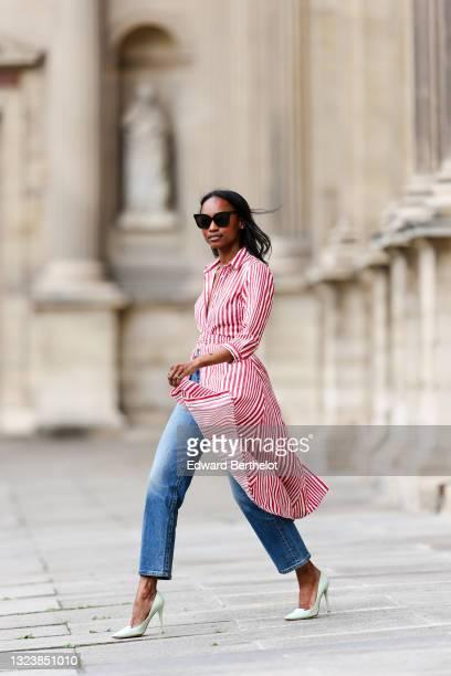Emilie Joseph @in_fashionwetrust wears black sunglasses, diamond earrings, a long red and white stripes belted shirt dress, blue denim hight jeans...