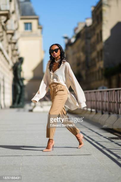 Emilie Joseph @in_fashionwetrust wears black sunglasses, silver earrings, a flowing oversized/Maxi shirt with collar in beige silk , vintage High...