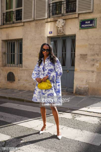Emilie Joseph @in_fashionwetrust wears sunglasses, a blue and white Toile de Jouy shirt short dress from Moschino, a yellow shiny lime satin pouch...