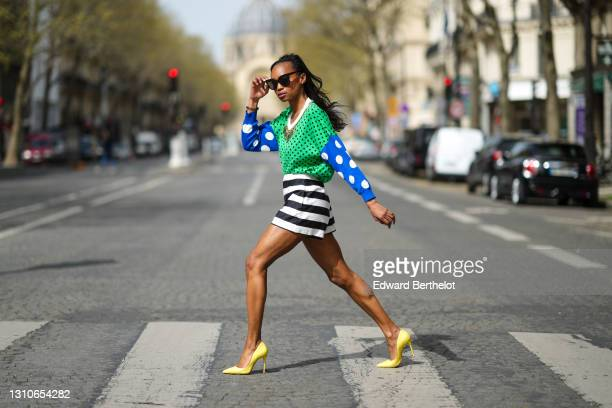 Emilie Joseph @in_fashionwetrust wears sunglasses, a large Moschino metal necklace, a green and blue polka dot jumper top from Moschino, high waisted...