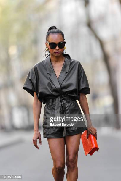 Emilie Joseph @in_fashionwetrust wears sunglasses, a vintage soft leather oversized shirt tucked into leather shorts, zebra earrings from Rixo...