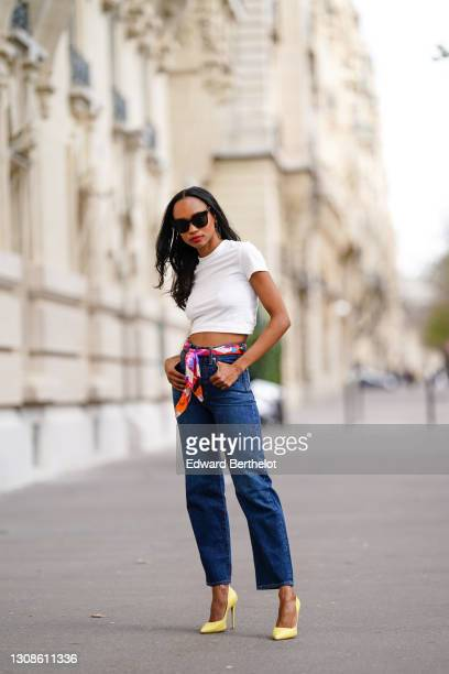 Emilie Joseph @in_fashionwetrust wears sunglasses, a white crew neck crop top from H&M, high rise ribcage straight blue jeans in dark indigo from...