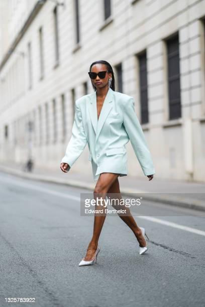 Emilie Joseph @in_fashionwetrust wears sunglasses, long bejeweled earrings from Isabel Marant, a pale green oversized blazer jacket worn as a dress,...