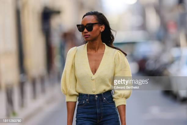 Emilie Joseph @in_fashionwetrust wears sunglasses, pale pastel yellow a puffed sleeves wool cardigan from Mango, high rise blue denim jeans pants...