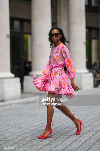 Emilie Joseph @in_fashionwetrust wears sunglasses, silver earrings, a Rhode printed summer vacay Ella dress in vibrant pink with long dolman sleeves...