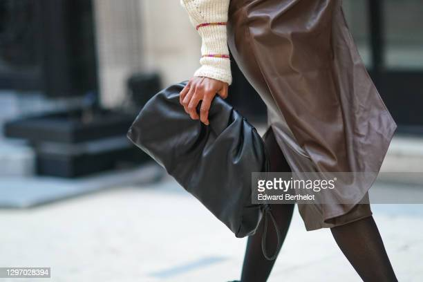 Emilie Joseph wears a brown leather skirt from Zara, black tights, a black leather bag from Mango, on January 09, 2021 in Paris, France.