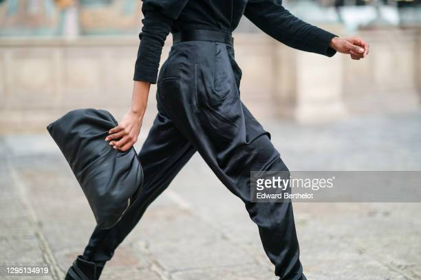 Emilie Joseph wears black shiny lustrous silky pants from Balmain, a black leather bag from Mango, from on January 07, 2021 in Paris, France.