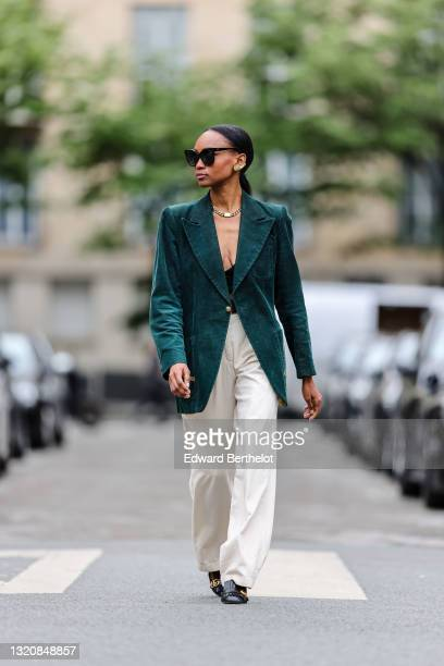 Emilie Joseph wears black sunglasses, gold earrings, a gold large chain necklace, a black silk V-neck crop top top / satin bralette, a dark green...