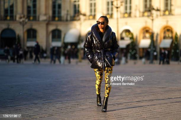 Emilie Joseph wears sunglasses, a black shiny oversized winter puffer jacket with oversized lapels from Gina Tricot, yellow and black floral print...