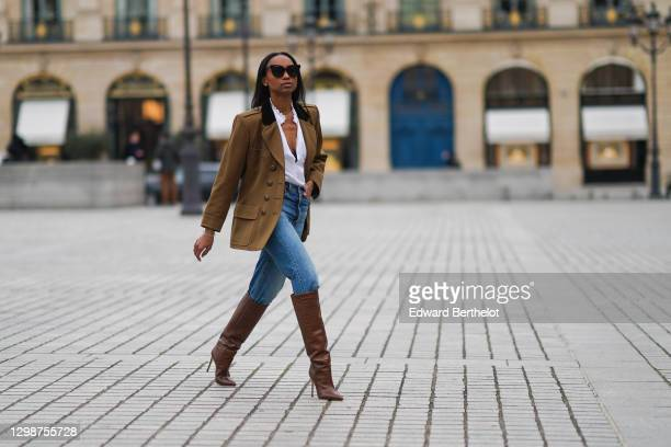Emilie Joseph wears sunglasses, a khaki military jacket from Saint-Laurent YSL, a white shirt / blouse from Zara with ruffled collar, blue denim...