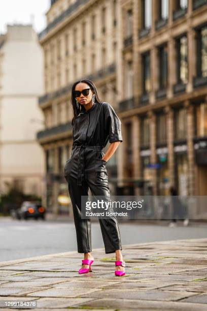 Emilie Joseph wears sunglasses from Gentle Monster, bejeweled earrings from Isabel Marant, a black leather jumpsuit from Mango, pink bejeweled heels...