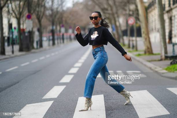 Emilie Joseph wears sunglasses, Isabel Marant bejeweled long earrings, a cropped black pullover with printed angels from Fiorucci, blue ribcage...