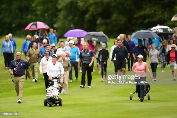 Emilie Overas of Norway and Lily May Humphreys of England walk up the 13th hole followed by crowds during the final of the Girls' British Open...
