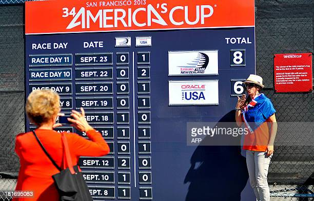 Emilie Rohrbach poses for a photo in front of a scoreboard after Oracle Team USA won race 16 of the 34th America's Cup on September 23 2013 in San...