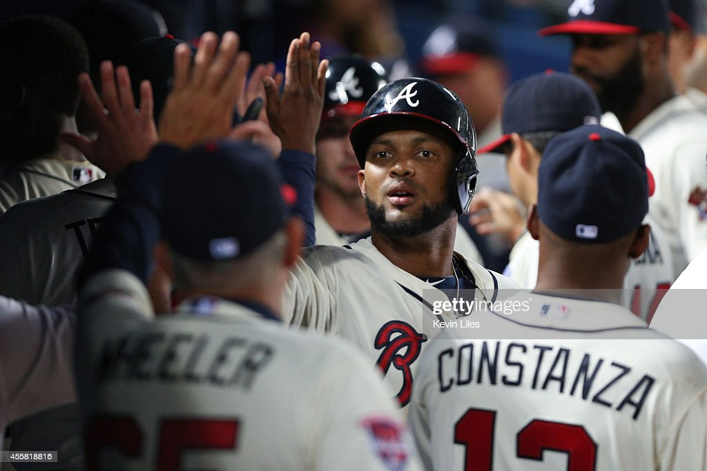 Emilio Bonifacio #1 of the Atlanta Braves is congratulated in the dugout after scoring during the 8th inning against the New York Mets at Turner Field on September 20, 2014 in Atlanta, Georgia.