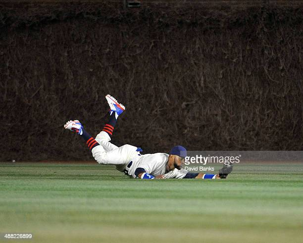 Emilio Bonifacio of the Chicago Cubs makes a catch on Mark Ellis of the St. Louis Cardinals during the seventh inning on May 4, 2014 at Wrigley Field...