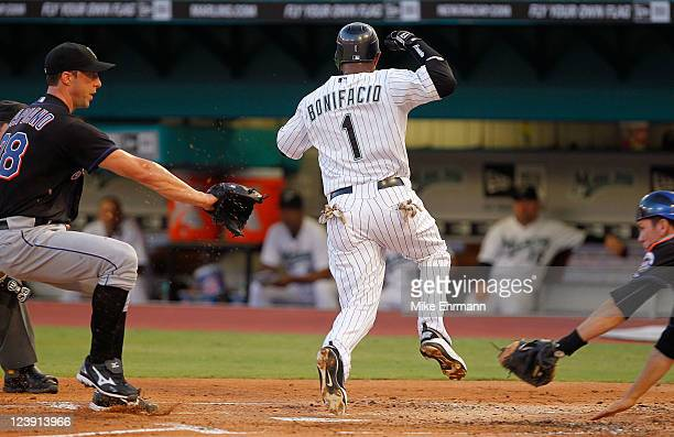 Emilio Bonifacio of the Florida Marlins scores on a wild pitch avoiding Chris Capuano and Josh Thole of the New York Mets during a game at Sun Life...