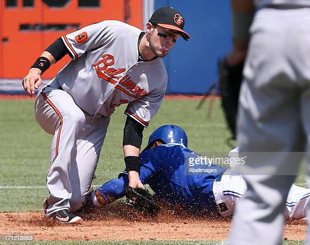 Emilio Bonifacio of the Toronto Blue Jays slides safe in the second inning past Ryan Flaherty of the Baltimore Orioles during MLB action at the...
