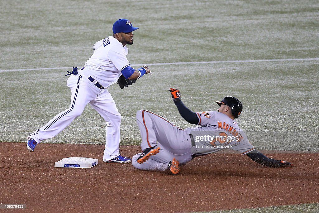 Emilio Bonifacio #1 of the Toronto Blue Jays turns a double play in the first inning during MLB game action as Nick Markakis #21 of the Baltimore Orioles slides into second base on May 23, 2013 at Rogers Centre in Toronto, Ontario, Canada.
