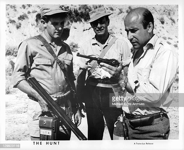 Emilio Caba Alfredo Mayo looking at the gun that Jose Prada displays to them in a scene from the film 'The Hunt' 1967