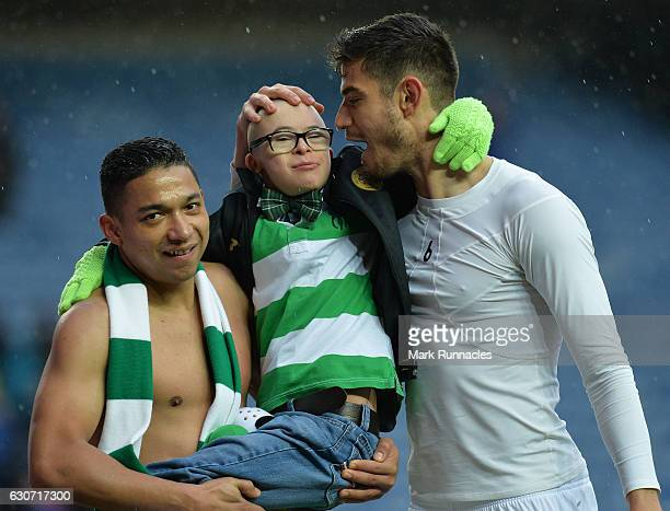 Emilio Izaguirre and Nir Bitton of Celtic celebrate at the final Whistle with a young fan during the Scottish Premiership match between Rangers FC...