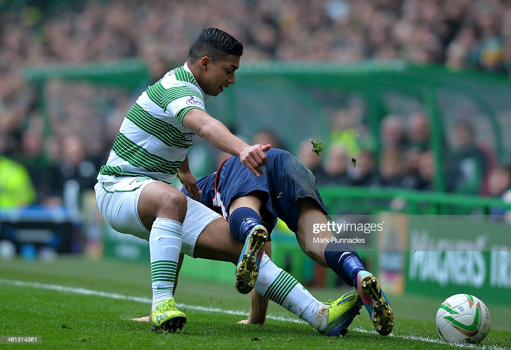 Emilio Izaguirre of Celtic and Richard Brittain of Ross County challenge during the Scottish Premier League match between Celtic and Ross County at Celtic Park Stadium on March 29, 2014 in Glasgow, Scotland.