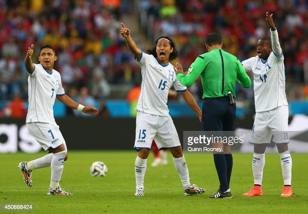 Emilio Izaguirre , Roger Espinoza and Oscar Boniek Garcia of Honduras protest France's second goal with referee Sandro Ricci during the 2014 FIFA...