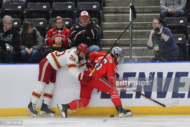 Emilio Pettersen of the Denver Pioneers checks Quinn Preston of the Ohio State Buckeyes into the boards in the first period during an NCAA Division I...