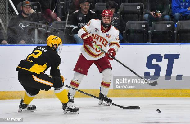 Emilio Pettersen of the Denver Pioneers passes the puck against Nicolas Luka of the American International Yellow Jackets during the NCAA Division I...