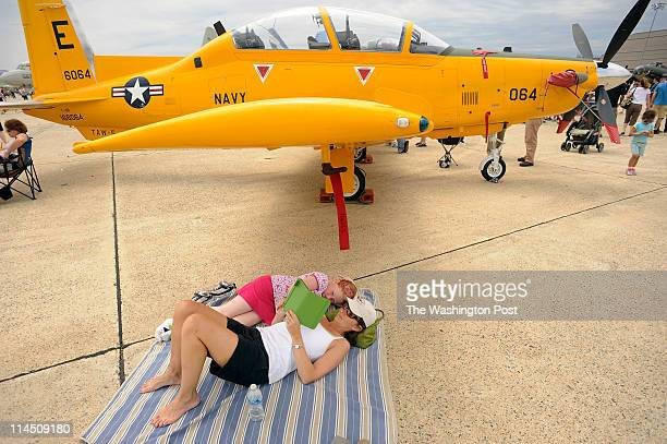 Emily Ambery and her mother Amy Ambery find shade under the wing of a T6B Texan II during the 2011 Joint Service Open House and Air Show on Sunday...