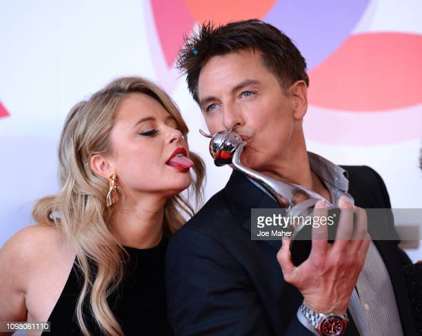 Emily Atack and John Barrowman pose with The Bruce Forsyth Entertainment Award for I'm A Celebrity… Get Me Out Of Here in the winners room during the...