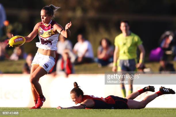 Emily Bates of the Lions kicks the ball from Daisy Pearce of the Demons during the round five AFLW match between the Melbourne Demons and the...