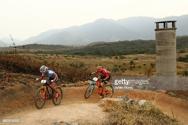 Emily Batty of Canda leads Annika Langvad of Denmark during the Women's Cross-Country Mountain Bike Race on Day 15 of the Rio 2016 Olympic Games at...