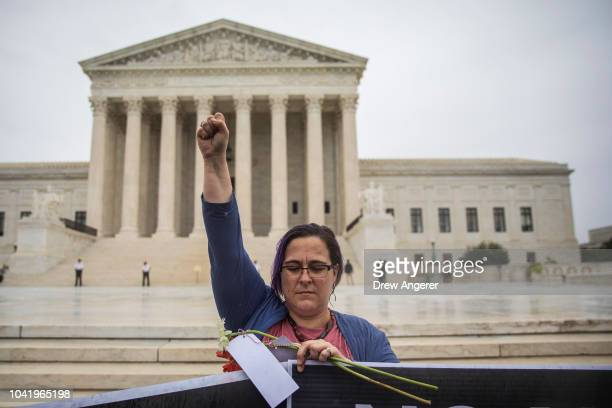Emily Brown, from Washington, DC, raises her fist as she protests against Supreme Court nominee Judge Brett Kavanaugh outside the Supreme Court,...