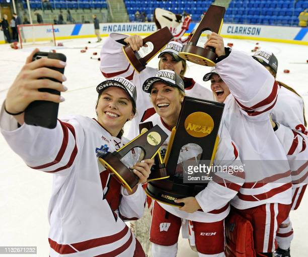 Emily Clark of the Wisconsin Badgers takes a photo with teammates and the NCAA Photos via Getty Images championship trophy as they celebrate their 20...