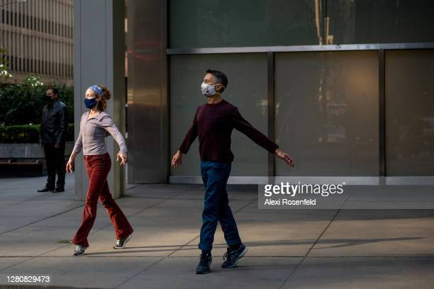 Emily Coates and another performer wearing masks dance outdoors during the Diagonal Redux performance by Yvonne Rainer on October 17, 2020 in New...
