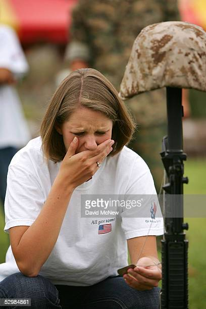 Emily Dierhuf cries as she holds the dog tag of her husband, U.S. Marine Cpl. Nicholas Dierhuf, who was killed three months after they were married,...