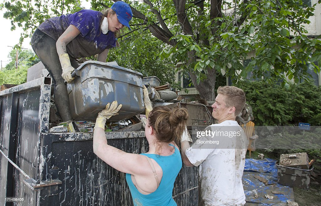 Emily Ebbels, left, Kyli Lane, center, and Charlie Hogarth help a friend's family clean up in Rideau Park after flooding in Calgary, Alberta, Canada, on Monday, June 24, 2013. Water levels in Calgary subsided and crews are working to restore power as officials confirmed a fourth fatality in the worst flood in Alberta's history. Photographer: Keith Morison/Bloomberg via Getty Images