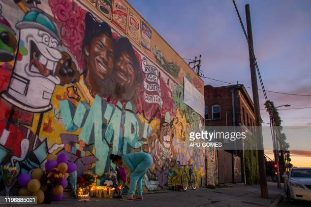 Emily Garbutt lights a candle below a mural by the artists Muck Rock and Mr79lts showing Kobe Bryant and his daughter Gianna Bryant who were killed...