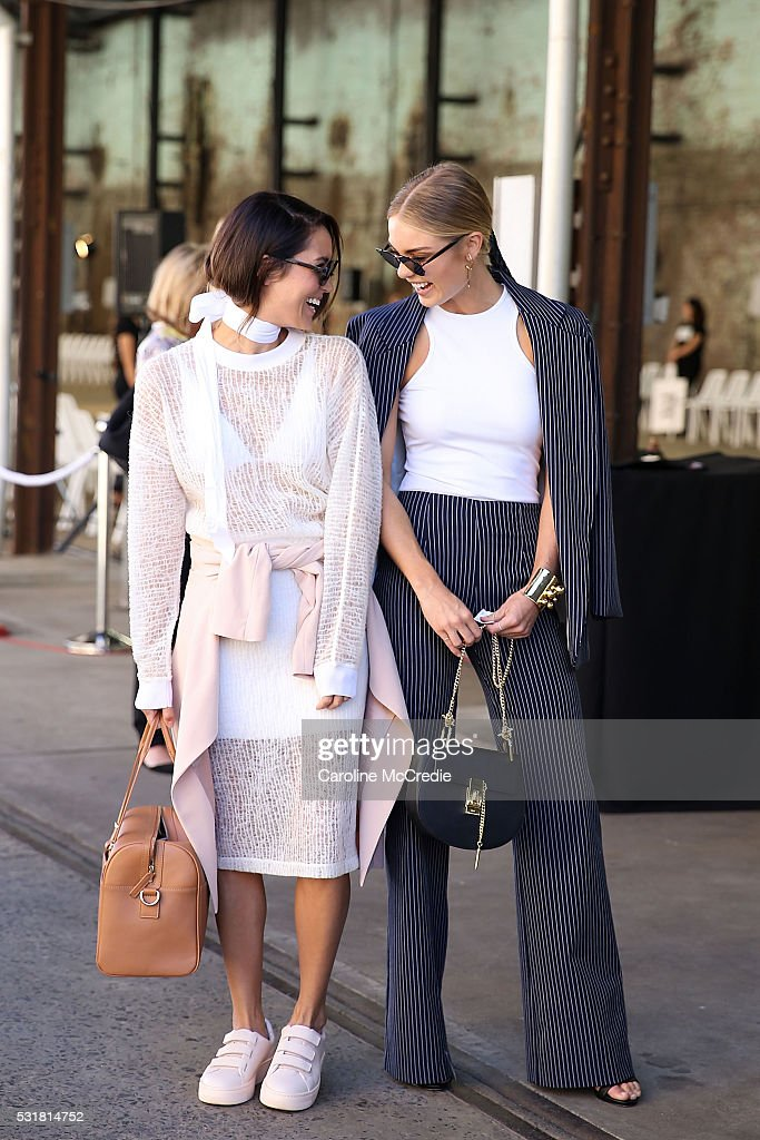 Emily Highfield, wearing Alexander Wang outfit, Sandro shoes and Karen Walker handbag, with Elyse Knowles, wearing By Johnny, arrive at the By Johnny show at Mercedes-Benz Fashion Week Resort 17 Collections at Carriageworks on May 17, 2016 in Sydney, New South Wales.