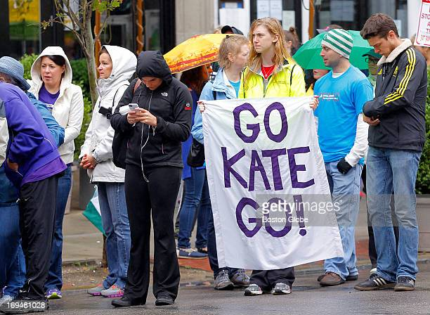 Emily Hutchinson of Newton holds a sign reading 'Go Kate Go' as she waits for her sister Kate to cross the Boston Marathon finish line on Boylston...