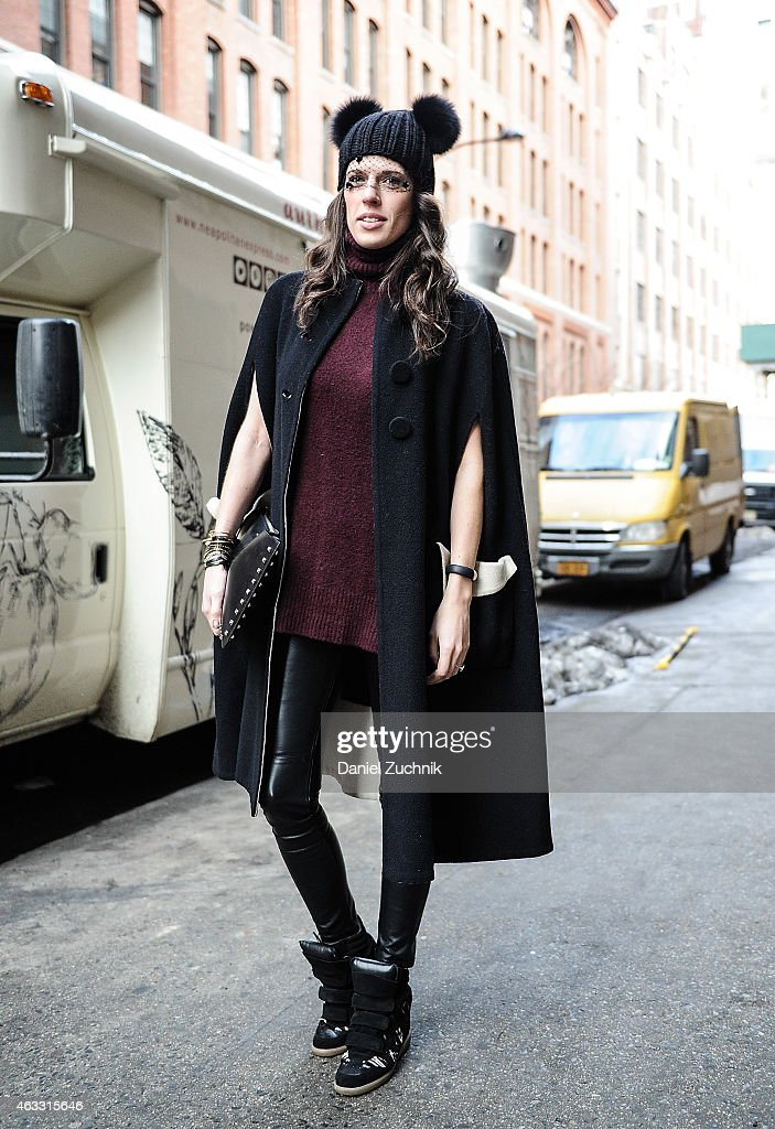 Emily Kammeyer is seen outside the Marissa Webb show wearing a Eugenia Kim hat, E. Kammeyer veil, vintage coat, H&M clutch and Isabel Marant sneakers on February 12, 2015 in New York City.