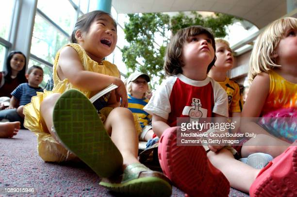 Emily Kang of Boulder left laughs at a part of a book being read by Melanie BorskiHoward for Storytime at the Boulder Public Library as Ada Urist...