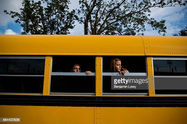 Emily Lampo and Jessica Meyer wait for their St Bernard Parish United School bus to leave the new school campus after the first day of classes...