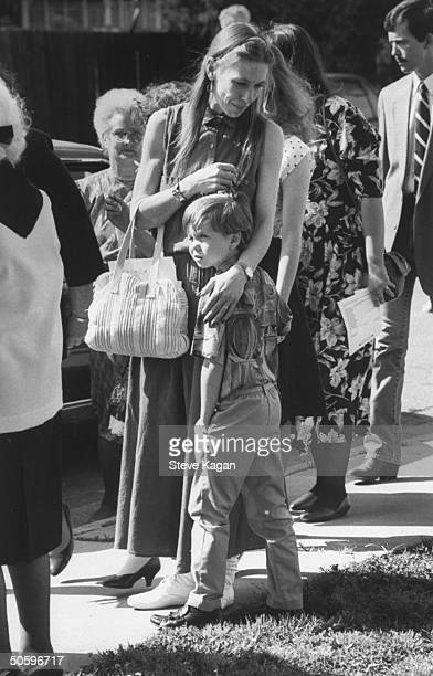 Emily Landrum aunt of murder victim Michael Moore holding 8yrold son Jed while standing outside the Holy Cross Episcopal Church at Michael's funeral...