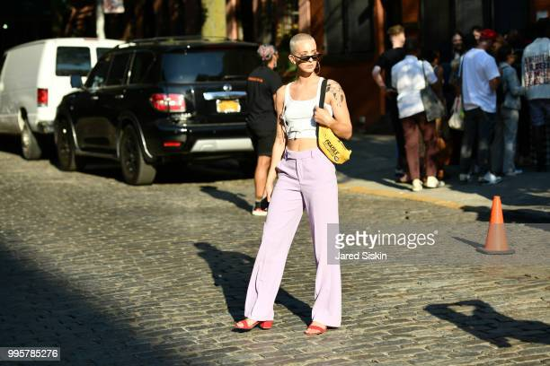Emily Lepsock is seen during July 2018 Men's Fashion week wearing a Dolls Co top Zara pants paired with a Petals and Peacocks hand bag outside of...