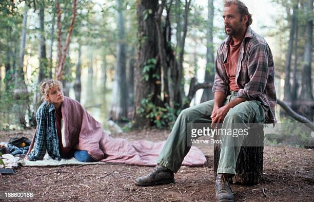 Emily Lloyd sitting on the ground with a blanket over her as Bruce Willis sits on a tree stump in a forest in a scene from the film 'In Country' 1989