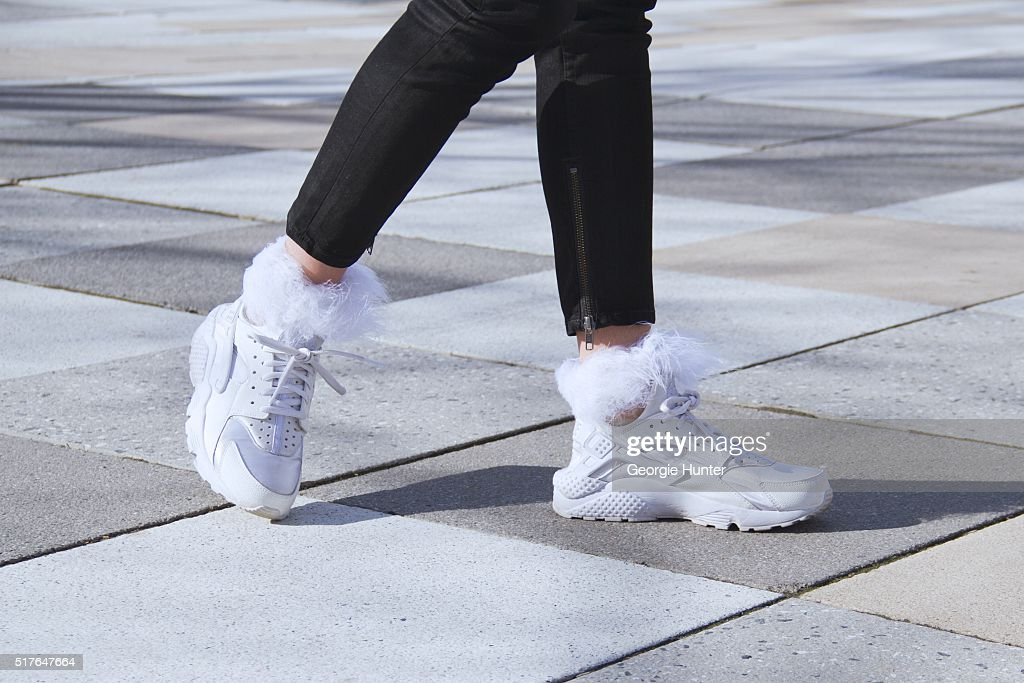 Emily Mercer wearing black BLK DNM pants with zip, white Nike sneakers and white socks with feather top by Rihanna with Stance on March 26, 2016 in New York City.